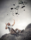 Some rocks falling on a scared man — Stock Photo