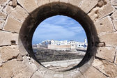 View of the coastal town Essaouira through a rampart hole. — Stock Photo