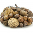 Mix nuts - walnuts, hazelnuts, almonds in a net bag on a white b — Stock Photo