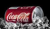Can of Coca-Cola on a bed of ice over a black background — Stock Photo
