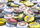 Pile of used bottle caps from assorted beers — Stock Photo