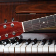 Guitar neck on old piano keys — Stock fotografie
