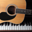 Guitar part on piano keys — Stockfoto #12896410