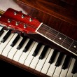 Guitar neck on old piano keys — Stockfoto