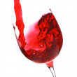 Red wine flow in a wineglass on white background - Stockfoto