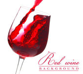 Red wine flow in a glass on white background — Stock Photo