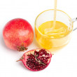 Stock Photo: Pomegranate and honey flowing in cup of glass on white