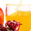 Stock Photo: Pomegranate and honey flowing in cup