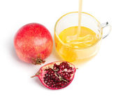 Pomegranate and honey flowing in a cup of glass on white — Stock Photo
