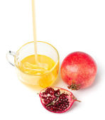Pomegranate and honey flowing in a cup of glass on white backgr — Stock Photo