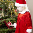 Little girl as Santa Claus by Christmas tree — Stock Photo #11430307