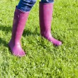 Detail of woman wearing rubber boots on spring meadow — Foto de Stock