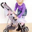 Little girl playing with a doll and a stroller — Stock Photo #13586056