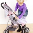 Little girl playing with a doll and a stroller — Stock Photo