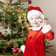 Stock Photo: Little girl as Santa Claus with Christmas present