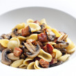 Pasta orecchiette with fried champignons and bacon - Stock Photo