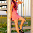 Young woman wearing pink dress standing on stairs — Stockfoto