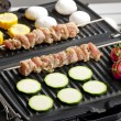 Meat skewers and vegetables on electric grill — Stock Photo #13586392