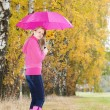 Woman wearing rubber boots with umbrella in autumnal nature — Foto de Stock