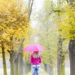 Stock Photo: Mother and her daughter with umbrellas in autumnal alley
