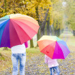 Mother and her daughter with umbrellas in autumnal alley — Stock Photo #13586840