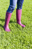 Detail of woman wearing rubber boots on spring meadow — Stock Photo