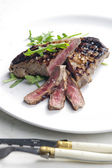 Grilled beefsteak pickled in Dijon mustard with ruccola — Stock Photo