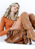 Sitting woman wearing fashionable brown boots with a handbag — ストック写真