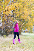 Woman wearing rubber boots in autumnal nature — Stock Photo