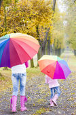 Mother and her daughter with umbrellas in autumnal alley — Stock Photo