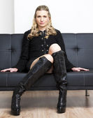 Woman wearing black clothes and boots sitting on sofa — Stock Photo