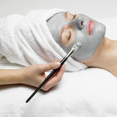 Application of a cosmetic mask on the face of young woman at the beautician — Stock Photo
