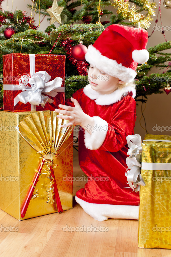 Little girl as Santa Claus with Christmas present — Stock Photo #13586152
