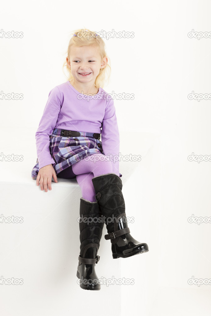 little girl wearing boots sitting on chair � stock photo