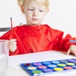 Little girl painting with watercolors - Stock Photo