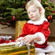 Little girl as Santa Claus with Christmas presents — Stock Photo #14120144