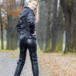 Woman wearing black clothes and boots in autumnal alley — Stock Photo #14120322
