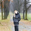 Woman wearing black clothes and boots in autumnal alley — Stock Photo #14120330