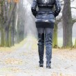Detail of woman wearing black clothes and boots in autumnal alle — Stock Photo