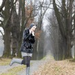 Woman wearing rubber boots in autumnal alley — Stock Photo #14936901