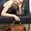 Portrait of woman with a handbag lying on sofa — Stock Photo
