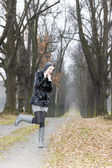 Woman wearing rubber boots in autumnal alley — Stock Photo