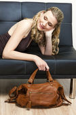 Portrait of woman with a handbag lying on sofa — Stock Photo
