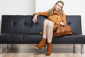 Woman wearing brown coat with a handbag sitting on sofa — Stockfoto