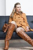 Kobieta nosi brązowy płaszcz, siedząc na kanapie — Zdjęcie stockowe