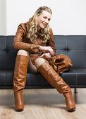 Kobieta nosi brązowy kurtka i buty, siedząc na kanapie — Zdjęcie stockowe