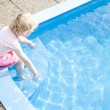 Little girl sitting by swimming pool — Stock Photo
