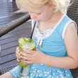Stock Photo: Portrait of little girl with a glass of cocktail