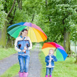 Mother and her daughter with umbrellas in spring alley — Stock Photo #18517319
