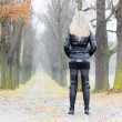 Woman wearing black clothes and boots in autumnal alley — Stock Photo